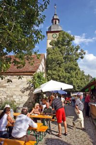 Feiern vor historischen Mauern: Straßenweinfest in der Kirchenburg in Hüttenheim.