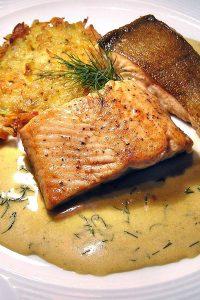 Unwiderstehlich lecker: Lachs vom Grill mit Gemüsepuffer und Kürbis-Dill-Sauce.