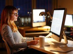 Frau arbeitet im Büro bis in die Nacht hinein - Schichtarbeiter