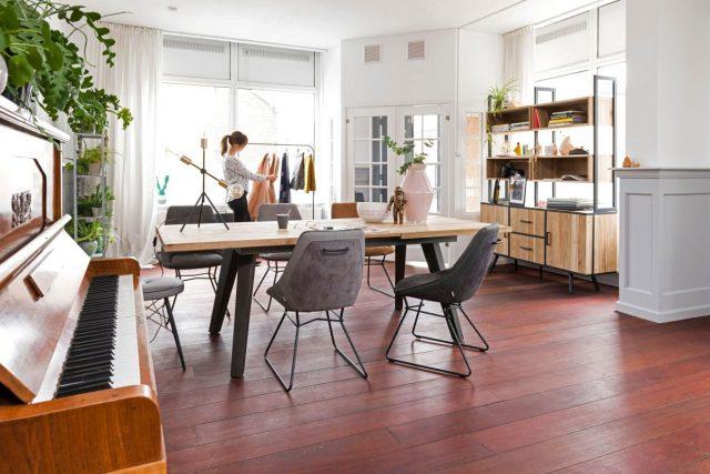 Helle Wände, ein Tisch mit Holzplatte und Sessel im Retro-Design ergeben eine stimmige Einrichtung.