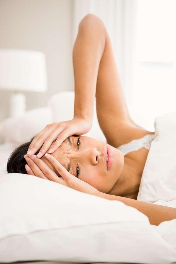 Migräneanfälle senken: Viele Migränepatientinnen wachen morgens schon mit den bohrenden Kopfschmerzen auf.
